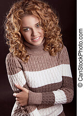 Attractive smiling woman wearing in sweater isolated on black background