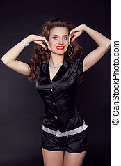 Attractive smiling woman with beauty long brown hair over dark posing at studio