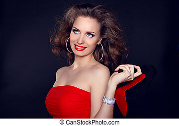 Attractive smiling woman with shoe portrait on dark background