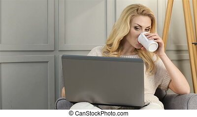 Attractive smiling woman working on laptop