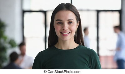 Attractive smiling young businesswoman professional looking at camera in office