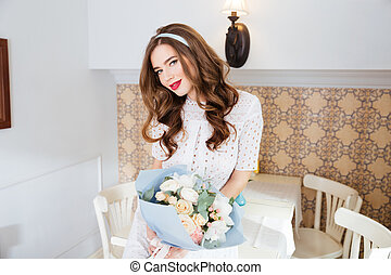 Attractive smiling young woman holding bouquet of flowers in cafe