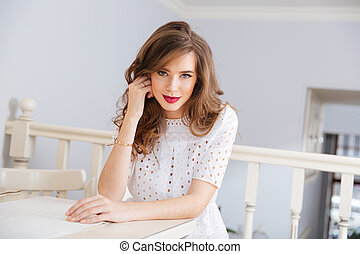 Attractive smiling young woman in white dress at cafe
