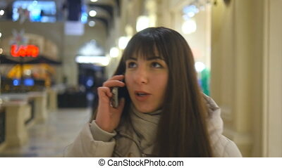 Attractive smiling young woman in winter clothes walk at the shopping mall and speaking on mobile phone. Girl going along the store and talking on cellphone. Close up of cute brunette female shopper