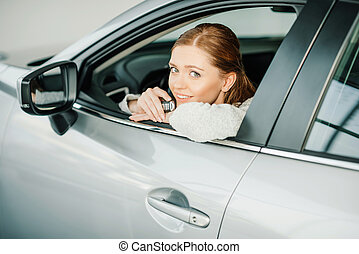 Attractive smiling young woman sitting in new car and holding key