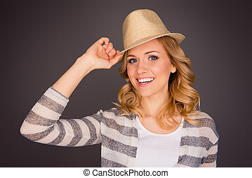 Attractive smiling young woman wearing hat on gray background