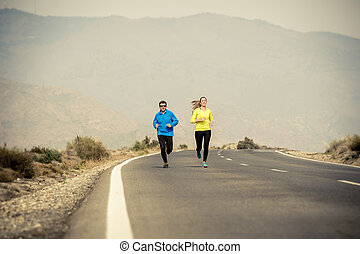 attractive sport couple man and woman running together on asphalt road mountain landscape