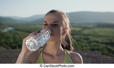 Attractive sport girl drinking cold water after running in the mountain in the fresh air during sunny day. Beautiful fitness athlete woman drinking water after work out, health and sport