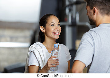 attractive sports people are talking and smiling in gym