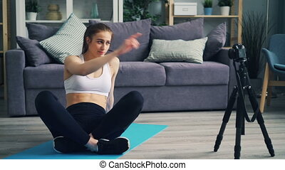 Attractive sportswoman blogger recording video with camera...