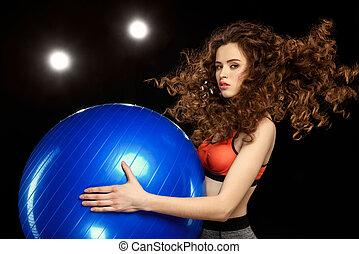 attractive sportswoman holding fitness ball on black