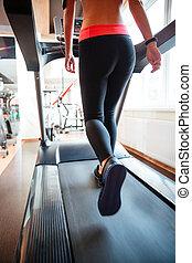 Attractive sportswoman running on treadmill in gym - Back...