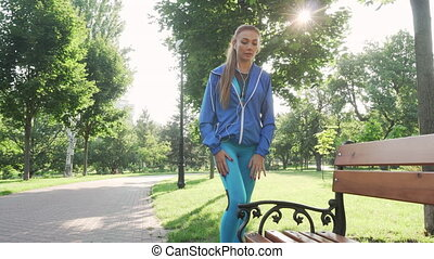 Attractive sportswoman stretching outdoors in the park. Low...