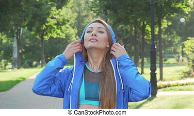 Attractive sportswoman taking off the hood before running in...