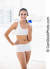 Attractive sporty brunette woman holding a water bottle