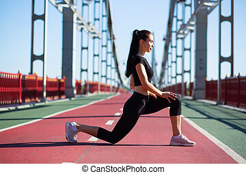 Attractive sporty girl stretching legs before run. Space for text