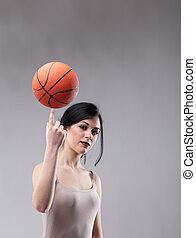 Attractive sporty woman balancing a basketball