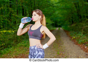 Attractive sporty woman drinking water from a bottle after joggi