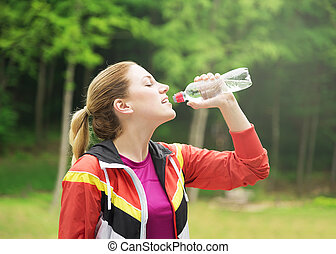 Attractive sporty woman drinking water .