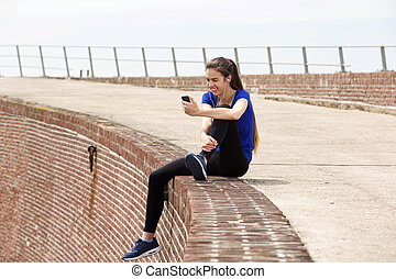 Attractive sporty woman sitting on wall with music