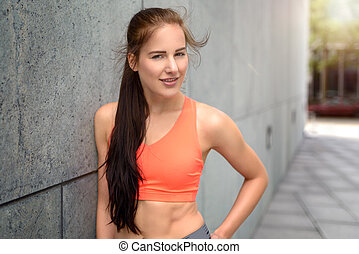 Attractive sporty young woman leaning on a wall
