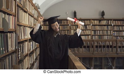 Attractive student in academic dress is having fun, standing in library.