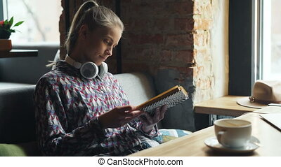 Attractive student reading book in cafe turning pages...