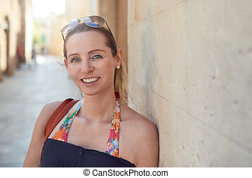 Attractive stylish woman relaxing against a wall