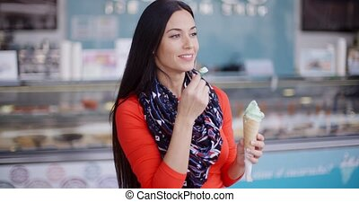 Attractive stylish young woman in a delicatessen eating an...