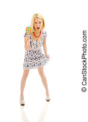 Attractive surprised blonde with lollipop holding her dress,...