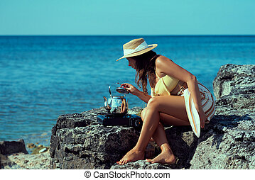 Attractive tanned girl in hat sitting on the stoned beach picking up a lid from kettle on propane stove.