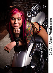 Attractive tattooed girl sitting on a big chopper, smiling
