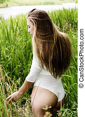 Attractive Teen Woman Standing In Grass At River
