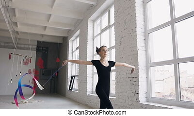 Attractive teenage girl gymnast dancing with colored ribbon in sport gym in white background near windows. Attractive girl gymnast jumping with ribbon in sport school