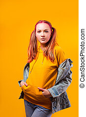 Attractive teenage girl holding her belly on yellow background
