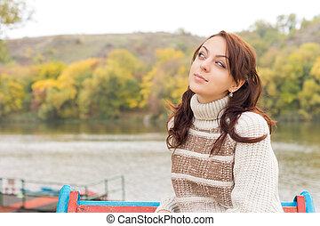 Attractive teenage girl sitting at a lake
