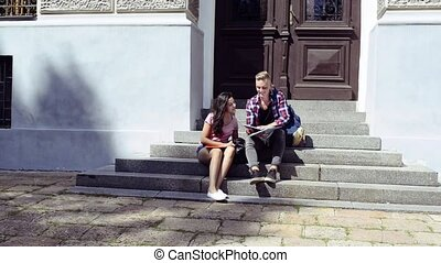 Attractive teenage student couple in front of university. -...