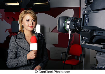 Television news reporter in live transmission smiling in front of the video camera in studio