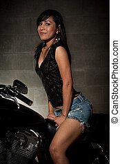 Attractive thirties asian woman riding motorcycle -...