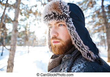 Attractive thoughtful bearded young man in winter hat
