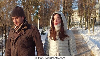 Attractive thoughtful man and woman walking in winter park holding hands 4K steadicam shot