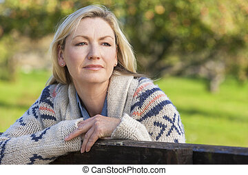 Attractive Thoughtful Middle Aged Woman Resting on Fence