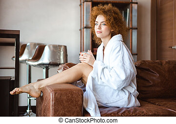 Attractive thoughtful woman in white bathrobe sitting on brown sofa