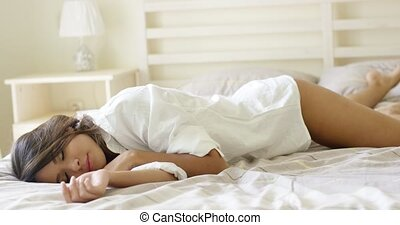 Attractive tired young woman relaxing on her bed