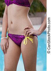 Attractive twenties asian woman by poolside