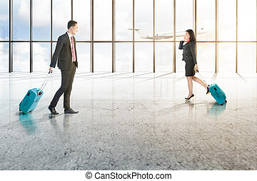 Attractive two asian business people with mobile phone and blue suitcases walking on the airport hall