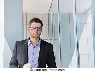 attractive urban businessman with coffee in hands on office buil