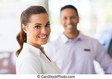 vehicle sales woman standing in front of colleague