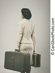 Attractive vintage woman with suitcases rear view - ...