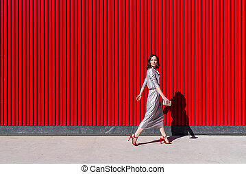 Attractive woman against a red wall outdoors